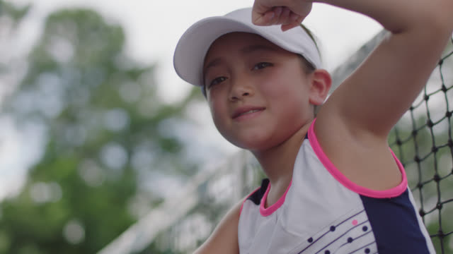 slow mo. cu. portrait of athletic female tennis player sitting on a tennis court smirking at the camera - sun visor stock videos and b-roll footage