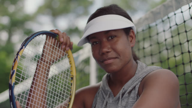 slow mo. cu. portrait of athletic female tennis player sitting on a tennis court smirking at the camera - tennis racket stock videos & royalty-free footage