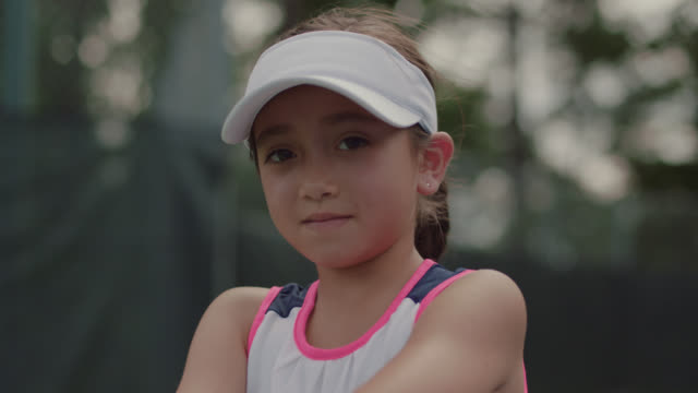 cu. portrait of athletic little girl sitting standing on a tennis court smiling at the camera - persistence stock videos & royalty-free footage