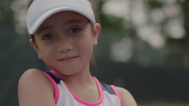 slow mo. cu. portrait of athletic little girl sitting standing on a tennis court smiling at the camera - arms crossed stock videos & royalty-free footage