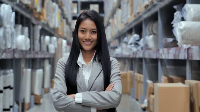 倉庫のカメラに微笑む折りたたみ式の腕を持って立つ企業のスーツを着た黒人女性起業家の肖像画。肖像画,ビジネス,金融,成功,リーダーシップ,stem,人,輸送 - 流通センター点の映像素材/bロール