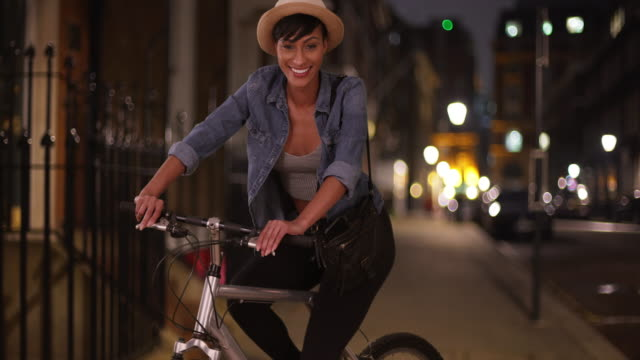 portrait of attractive african-american female on bicycle at night in city - hüfte stock-videos und b-roll-filmmaterial