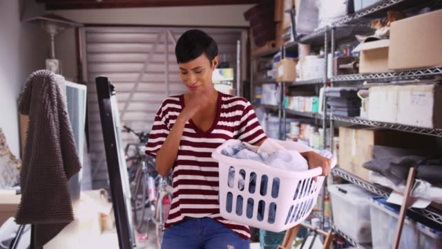 portrait of attractive black female holding basket of clean clothes and sneezing - hausarbeit stock-videos und b-roll-filmmaterial