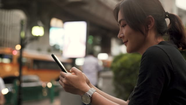 portrait of attractive smiling typing on the screen of the smartphone while chatting - thai ethnicity stock videos & royalty-free footage