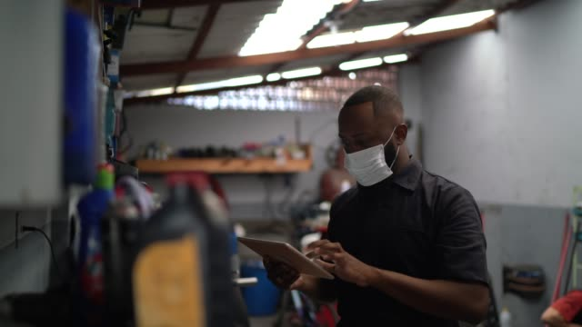 portrait of auto mechanic man using digital tablet at auto repair shop - african ethnicity stock videos & royalty-free footage