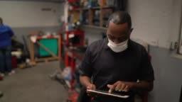 Portrait of auto mechanic man using digital tablet at auto repair shop