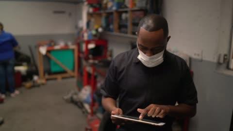 portrait of auto mechanic man using digital tablet at auto repair shop - brazilian ethnicity stock videos & royalty-free footage