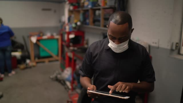 portrait of auto mechanic man using digital tablet at auto repair shop - mechanic stock videos & royalty-free footage