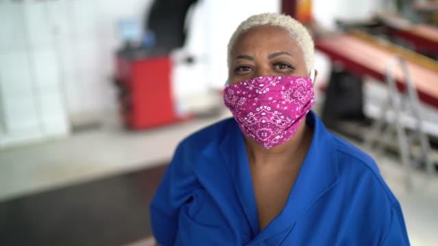 vídeos de stock, filmes e b-roll de retrato de mulher mecânica de automóveis na oficina de reparação de automóveis - indústria automobilística