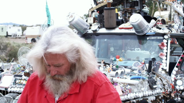 cu, portrait of baby boomer man putting on santa's hat standing in front of adorned truck, niland, california, usa - santa hat stock videos & royalty-free footage