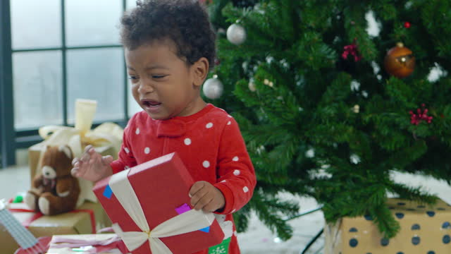 portrait of baby boy african ethnicity age 4 month disappointment emotion while opening xmas gift box while placing presents under the christmas tree.christmas spirit concept. - disappointment stock videos & royalty-free footage