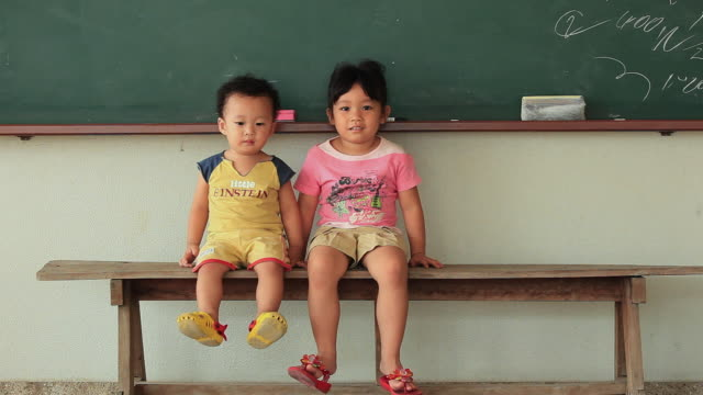 ws portrait of baby boy (18-23 months) and girl (4-5) sitting on bench in classroom / bangkok, thailand - 18 23 months stock-videos und b-roll-filmmaterial