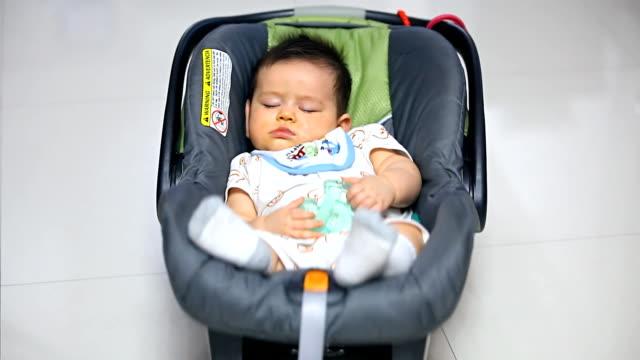 Portrait of baby boy sleeping in carseat.