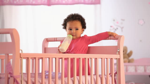 ms portrait of baby girl (19-23 months) drinking from baby bottle, standing in crib / richmond, virginia, usa - biberon video stock e b–roll