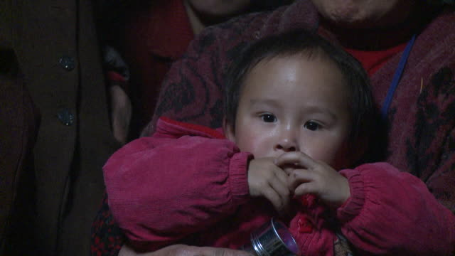 CU Portrait of baby girl sitting on grandmother's laps, Datong, Sichuan, China