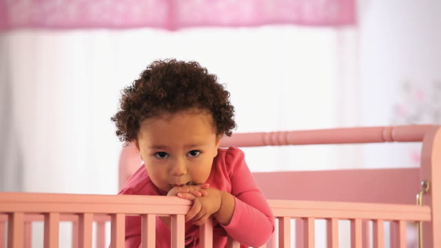 cu pan portrait of baby girl (19-23 months) standing in crib, smiling / richmond, virginia, usa - babies only stock videos & royalty-free footage