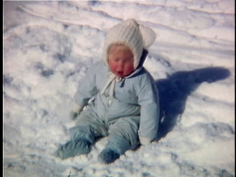 stockvideo's en b-roll-footage met 1963 ms portrait of baby girl wearing snowsuit sitting on snow, vermont, usa - 1963