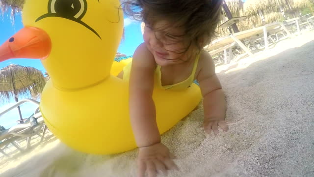 portrait of baby girl with inflatable swim ring on a beach - inflatable stock videos and b-roll footage