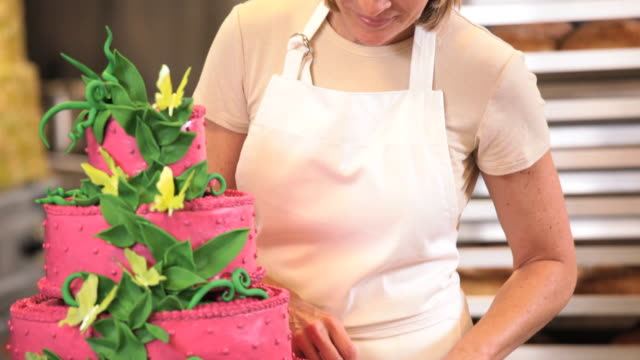 MS TU Portrait of Baker in Commercial Kitchen Applying Icing Flowers to Large Cake / Richmond, Virginia, USA