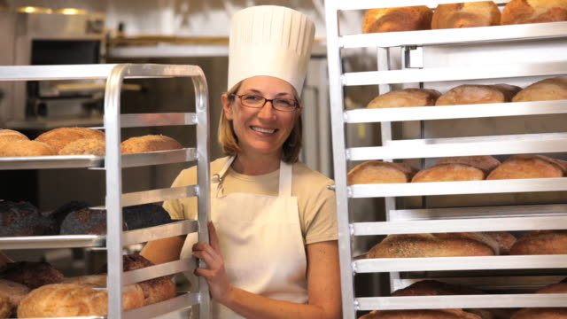 ms portrait of baker in commercial kitchen standing between racks of fresh bread / richmond, virginia, usa - chef's hat stock videos & royalty-free footage