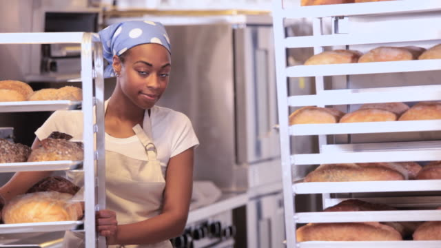ms portrait of baker in commercial kitchen standing between racks of fresh bread / richmond, virginia, usa - bakery stock videos and b-roll footage