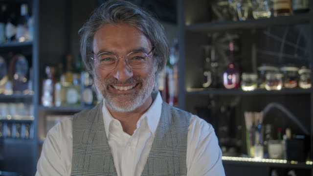 portrait of bar owner / bartender in his trendy, stylish, moody bar while night - toothy smile. - mature men stock videos & royalty-free footage