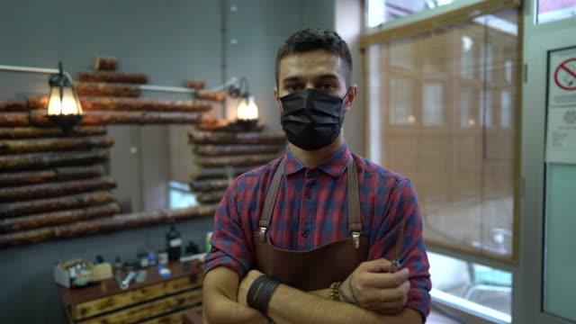 vídeos de stock, filmes e b-roll de retrato de barbeiro com máscara facial protetora em sua barbearia - salão de beleza