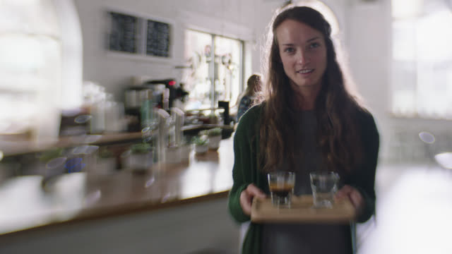 ms slo mo. portrait of barista holding tray with espresso shot and tonic in modern coffee shop. - tray stock videos and b-roll footage