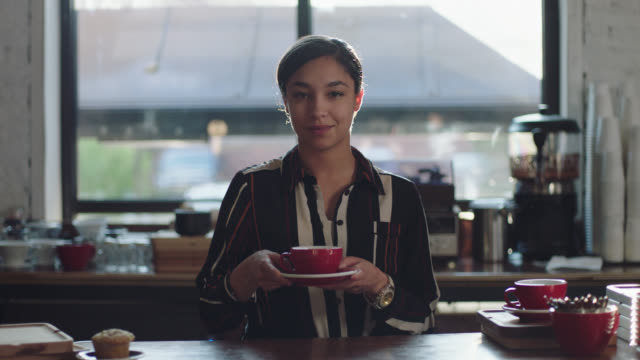 vídeos de stock, filmes e b-roll de ms slo mo. portrait of barista picking up mug and sipping coffee behind counter in local cafe. - xícara de café