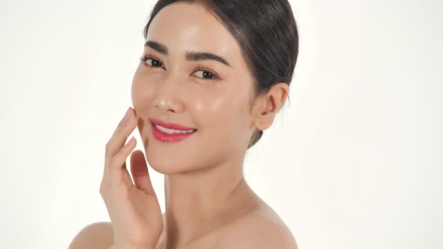白い背景に美しく、セクシーなアジアの女性の肖像画。幸せな感情で彼女の顔に触れる美しい女性。表情表現。美容とスパ.ビューティーフェイス.ビデオ:多様な肖像画 - 中国人点の映像素材/bロール
