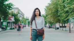 Portrait of beautiful Asian student stanidng in city street with serious face
