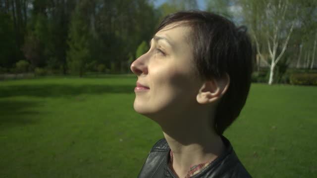 vidéos et rushes de portrait de belle femme de cheveu noir regardant l'appareil-photo et souriant, parc en arrière-plan - vêtement de sport