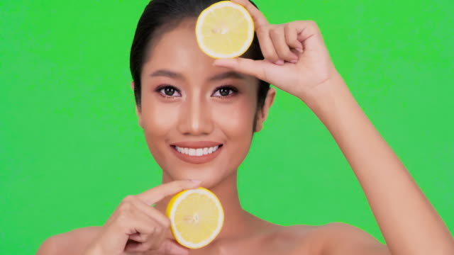portrait of beautiful black woman on green background with lemon slices in front of eyes.expressive facial expressions.cosmetology and spa.beauty face.green screen - lips stock videos & royalty-free footage