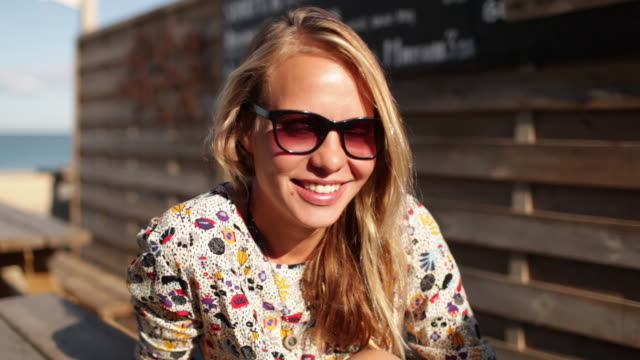 Portrait of beautiful blonde woman smiling at camera at beach bar in Southern France.