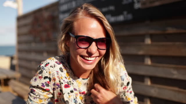 portrait of beautiful blonde woman smiling at camera at beach bar in southern france. - blonde hair stock videos & royalty-free footage