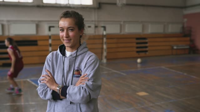stockvideo's en b-roll-footage met portret van mooie vrouwelijke basketbal coach - armen over elkaar
