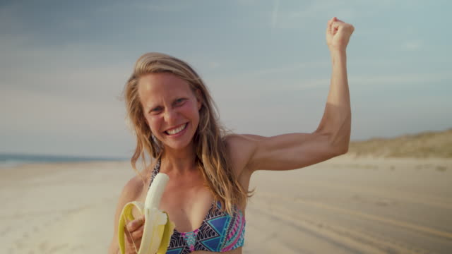 vidéos et rushes de portrait of beautiful female surfer eating banana, smiling on beach, getting ready for surf in bikini at atlantic ocean in the south of france - banane fruit exotique