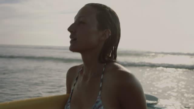 portrait of beautiful female surfer in bikini walking out of atlantic ocean waves in summer on deserted beach, carrying surfboard - セレクティブフォーカス点の映像素材/bロール