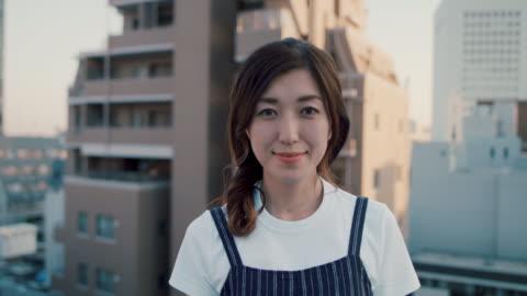 portrait of beautiful japanese woman on roof terrace in tokyo, japan. - aspirations点の映像素材/bロール
