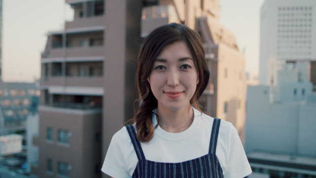 portrait of beautiful japanese woman on roof terrace in tokyo, japan. - 努力点の映像素材/bロール