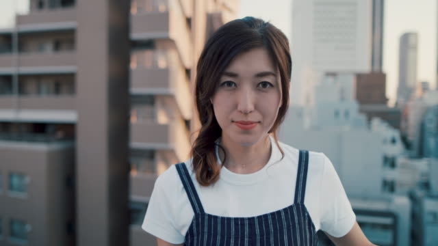 portrait of beautiful japanese woman on roof terrace in tokyo, japan. - ポートレート点の映像素材/bロール