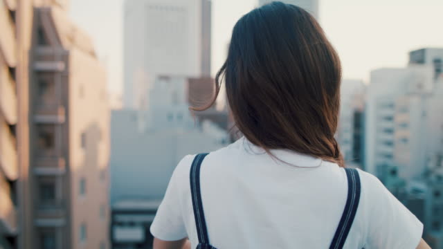 portrait of beautiful japanese woman on roof terrace in tokyo, japan. - balcony stock videos & royalty-free footage