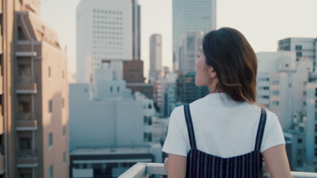 vidéos et rushes de portrait of beautiful japanese woman on roof terrace in tokyo, japan. - admirer le paysage