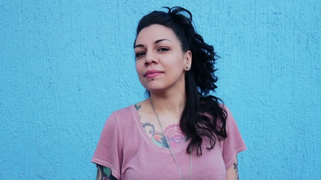 portrait of beautiful latina /mexican millennial woman with tattoos near blue background - headshot stock videos & royalty-free footage