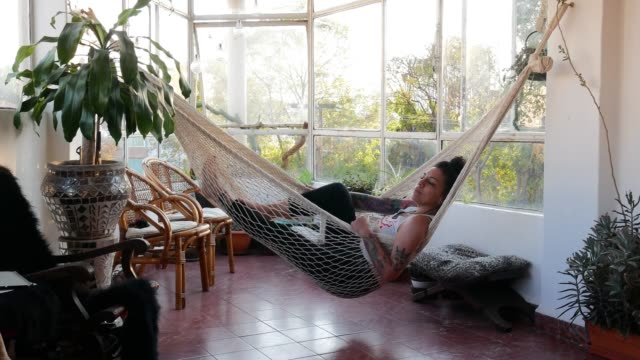 vídeos de stock e filmes b-roll de portrait of beautiful latina /mexican millennial woman with tattoos relaxing in hammock at home - cama de rede