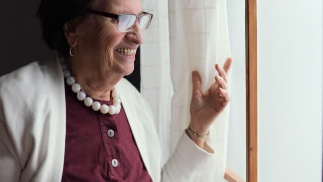 vídeos de stock, filmes e b-roll de retrato de uma bela mulher madura relaxante junto à janela. - mulheres idosas