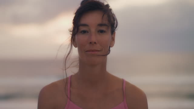 Portrait of beautiful mid adult woman practicing yoga on the beach at sunset at Atlantic ocean in the south of France.