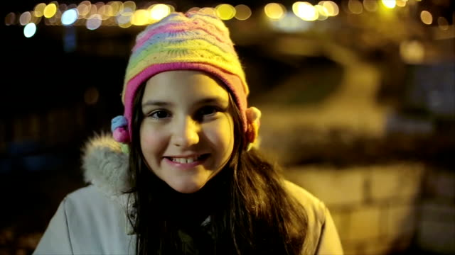 Portrait of beautiful pre-adolescent girl on the street at night