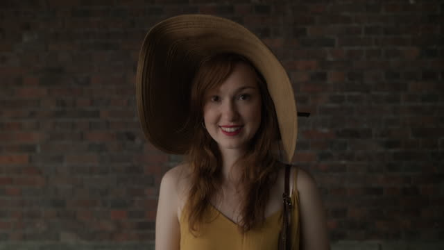 Portrait of beautiful red haired woman with large sun hat in front of brick wall, smiling into camera, looking happy in Berlin, Germany.