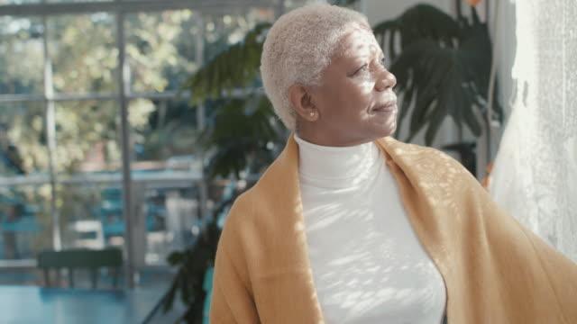 portrait of beautiful senior adult woman at home looking out of window - profil redigerat segment bildbanksvideor och videomaterial från bakom kulisserna